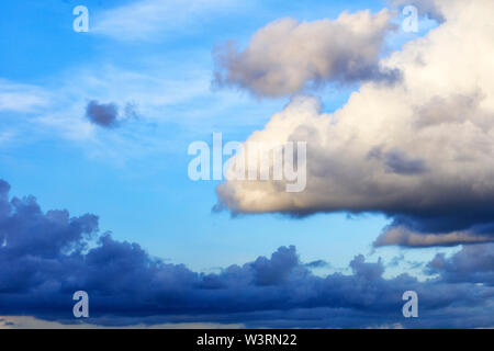 Thunderclouds float in the sky, gathering together. - Stock Photo