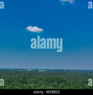 Horizontal aerial view to the horizon with blue sky, much copy space, a small cloud and windmills - Stock Photo