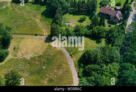 Aerial view of a meadow area with a few houses and a loose stock of bushes and trees. - Stock Photo