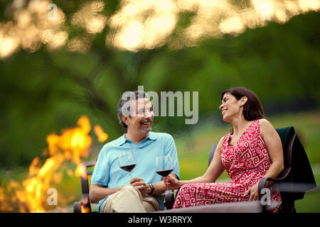 Smiling middle-aged couple relax with a glass of red wine beside a campfire in their garden in the late afternoon.