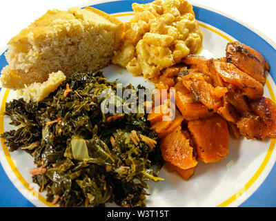 A plate of southern comfort food in America. A serving of kale greens, candied yams, macaroni and cheese, and cornbread. - Stock Photo