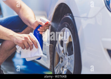Close up of man cleaning car wheel with cloth and spray bottle. - Stock Photo