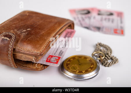 Leather wallet and an old watch on a white table. Personal documents in leather cover. Light background. - Stock Photo