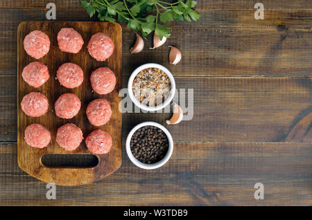 Raw meatballs on the cutting board on wooden surface. Top view, flat lay - Stock Photo