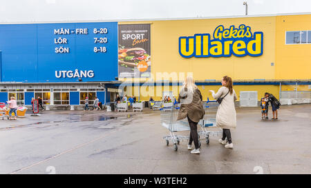 two women with shopping carts walking to the entrance of GeKås Ullared, Sweden, June 16, 2019 - Stock Photo