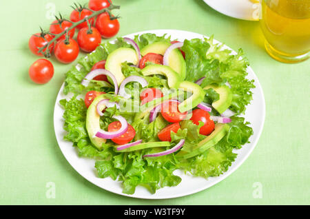 Vegetable salad with avocado, red onion and cherry tomatoes on white plate, close up - Stock Photo