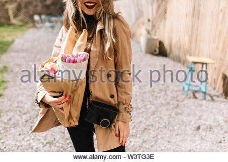 Happy long-haired girl in brown coat carries fresh flowers, apples and baguettes in a paper bag. Lovely woman posing after successful shoping on the blur street background. Female photographer - Stock Photo