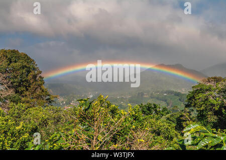 Image of a landscape in Boquete, Panama, including a beautiful and intense rainbow. The town of Boquete is in the middle ground, left. - Stock Photo