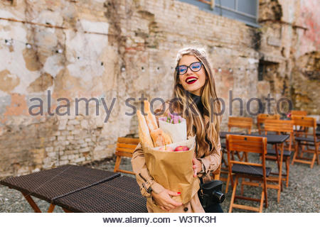 Attractive young woman came to outdoor cafe after food shopping and looks away. Stylish fair-haired girl in big glasses posing in front of old wall holding bakery bag and bouquet of purple flowers. - Stock Photo