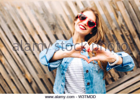 Portrait of young european woman in glasses making heart sign to express her love feelings. Charming girl in denim suit posing making love sign on the blur background. Focus on hands, body part - Stock Photo