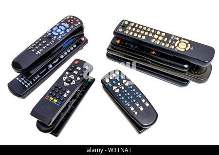 Horizontal shot of four stacks of old remote controls. White background. - Stock Photo