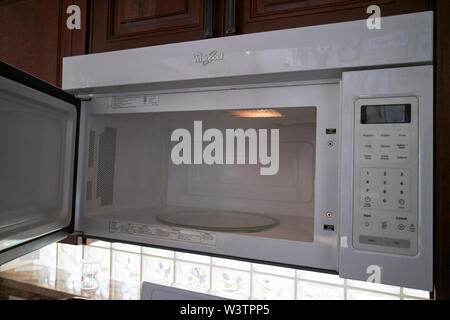 open door of a whirlpool microwave oven in a kitchen in the USA United States of America - Stock Photo