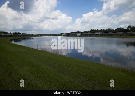 gated community surrounding an artificial lake in kissimmee florida USA United States of America - Stock Photo