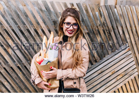 Cute stylish young woman goes to drink tea with friends carrying fresh baked goods and a bouquet. Pretty girl in glasses posing with a surprised smile holding paper bag with meal and flowers. - Stock Photo