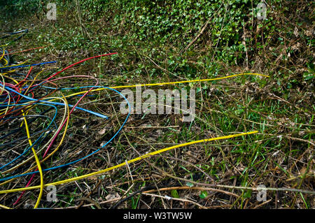 Coloured plastic cables dumped in a natural environment. - Stock Photo