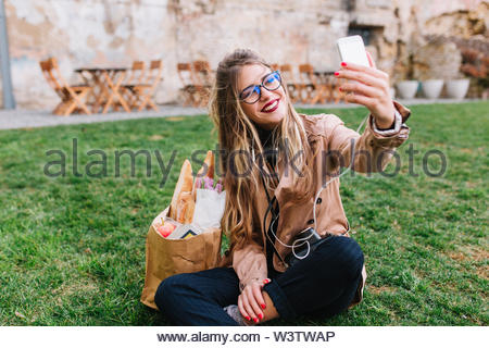 Cute blonde girl in glasses making selfie with hand up sitting on the green grass in park. Charming young woman taking rest after shopping and making photo for instagram profile with legs crossed - Stock Photo