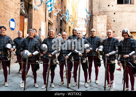 Men in historical medieval costumes line up in preparation for the parade of the Palio through the streets of Siena, Italy - Stock Photo
