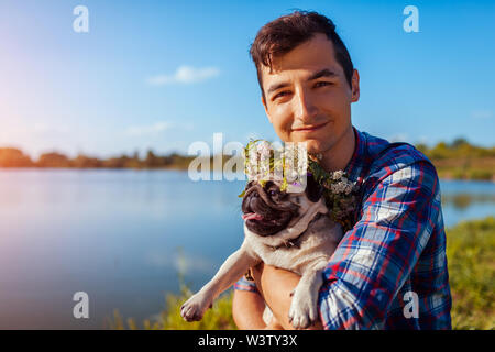 Man holding pug dog with flower wreath on head. Happy man walking with pet by summer lake - Stock Photo