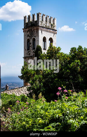 Medieval town hall tower and facade of Santa Maria Sopra Minerva, ancient church of Assisi, Umbria build over a roman age temple - Stock Photo