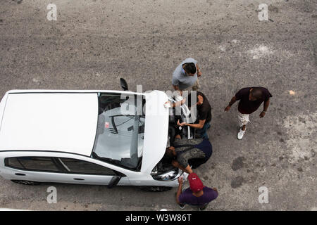 A group of men work on a car with the hood up on the street in Havana, Cuba - Stock Photo