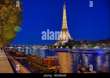 Paris, France - April 20, 2019 - A view of the Eiffel Tower at night across the River Seine in Paris, France. - Stock Photo
