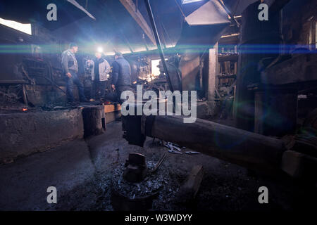 old mechanical hammer in blacksmith traditional workshop with workers and light flares in the background - Stock Photo