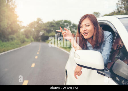 beautiful woman got new car. showing car key from window out of new car. - Stock Photo