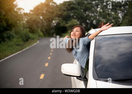 Relaxed happy woman on the road trip travel vacation leaning out car window. - Stock Photo