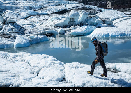 Glacier guide walking across the white ice of the Matanuska Glacier next to a calm lake. - Stock Photo