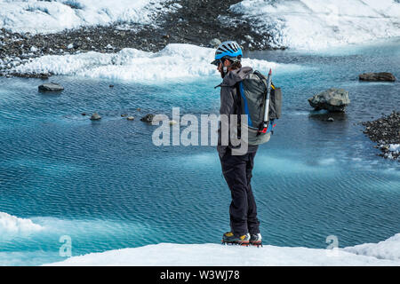 Young man standing with hands in pockets looking out over a blue pool on top of the white ice of the Matanuska Glacier in Alaska. - Stock Photo