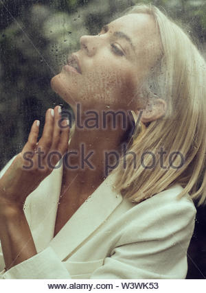 Close-up portrait of young blond woman behind window glass - Stock Photo