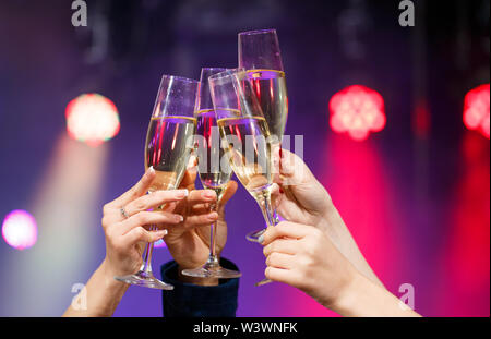 Clinking glasses of champagne in hands on bright lights background. - Stock Photo