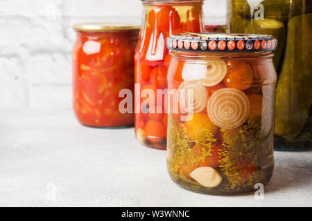Preservation of vegetables in banks. Fermentation products. Harvesting cucumbers and tomatoes for the winter - Stock Photo