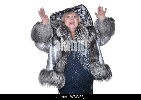 Portrait of senior woman wearing black hat and fur coat on white background - Stock Photo