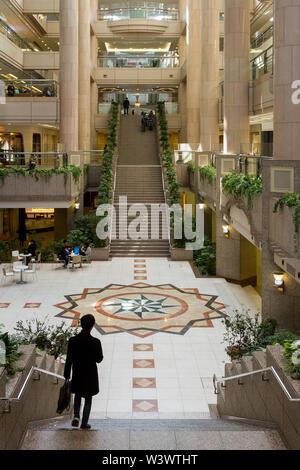 A man walks down stairs at Landmark Plaza under Landmark Tower Sakuragicho, Yokohama, Japan. Saturday March 2nd 2019 - Stock Photo