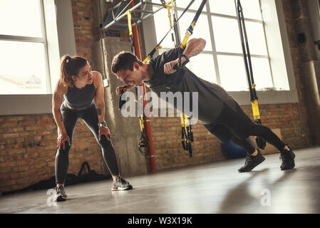 Giving motivation. Young and strong man in sportswear doing push ups with trx fitness straps and smiling while his personal trainer is standing close to him. TRX Training. Exercising together. Active couple