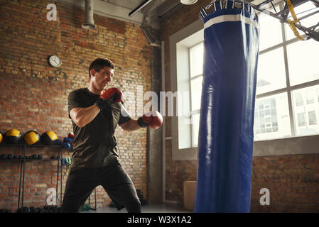 Strong and motivated. Young and sporty man boxing in gloves in a loft style gym. Boxer. Professional sport. Punching bag - Stock Photo
