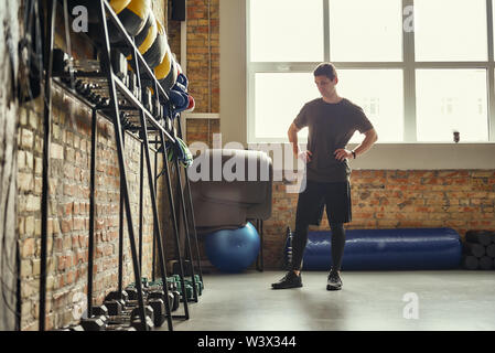 Ready for workout. Confident young man is looking at sport equipment while exercising at gym. Functional training. TRX Training. Healthy lifestyle - Stock Photo