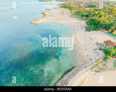 Aerial drone view of Holiday In Sanur Beach, Bali, Indonesia with ocean, boats, beach, villas, and people. - Stock Photo