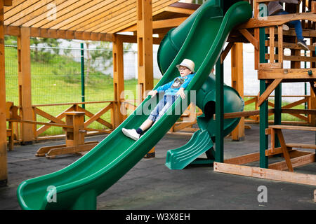 Child with straw hat and big glasses playing on outdoor playground. Active kid on colorful swing. Healthy summer activity for children. Little boy swi - Stock Photo