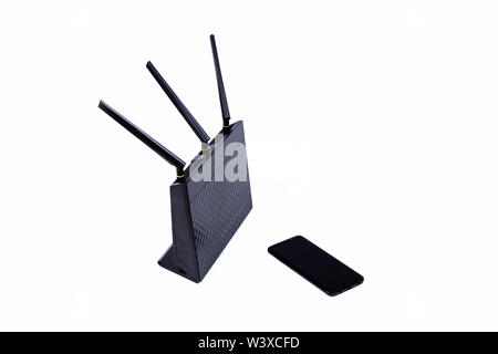 Black wireless wifi router cable modem and a modern no name smartphone isolated on white. Internet connectivity and general simple network topology - Stock Photo