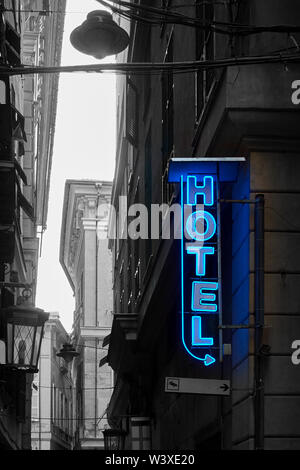 Illuminated neon hotel sign in the urban street. Partly black and white image - Stock Photo