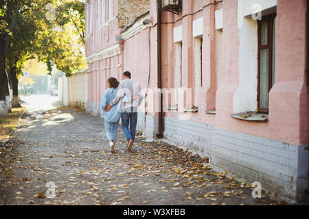 Back view of young hugging couple walking in park in autumn - Stock Photo