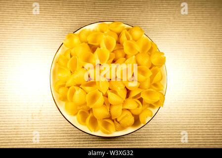 CONCHIGLIONI Italian dry raw pasta Top view. Selective focus with copy space for text. - Stock Photo
