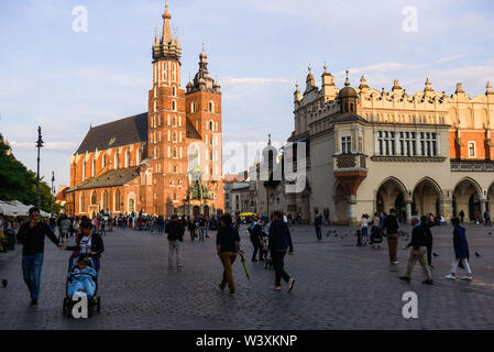 July 14, 2019 - Krakow, Poland - People walk past a St. Mary's Basilica and a Cloth Hall buildings at the Main Square in Kraków..Old Town is listed as a UNESCO World Heritage Site since 1978. (Credit Image: © Omar Marques/SOPA Images via ZUMA Wire) - Stock Photo