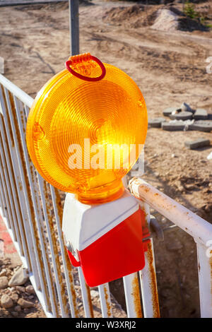 Yellow warning light on fence on the road. - Stock Photo