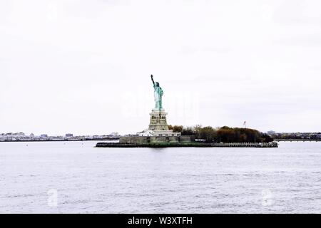 A distant wide shot of The Statue of Liberty with a clear white sky in the background - Stock Photo