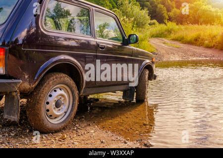 Off-road vehicle at a ford across the river in the glowing light of sunrise. Adventures in nature. - Stock Photo
