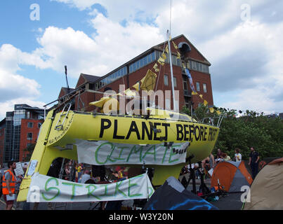 leeds, west yorkshire, united kingdom - 16 july 2019: the large yellow boat banners and people in the road at the extinction rebellion protest blockin - Stock Photo