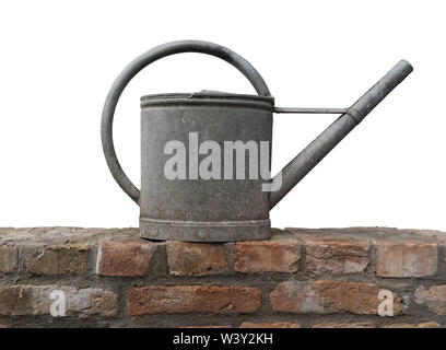 Old zinc watering can on a brick wall isolated - Stock Photo